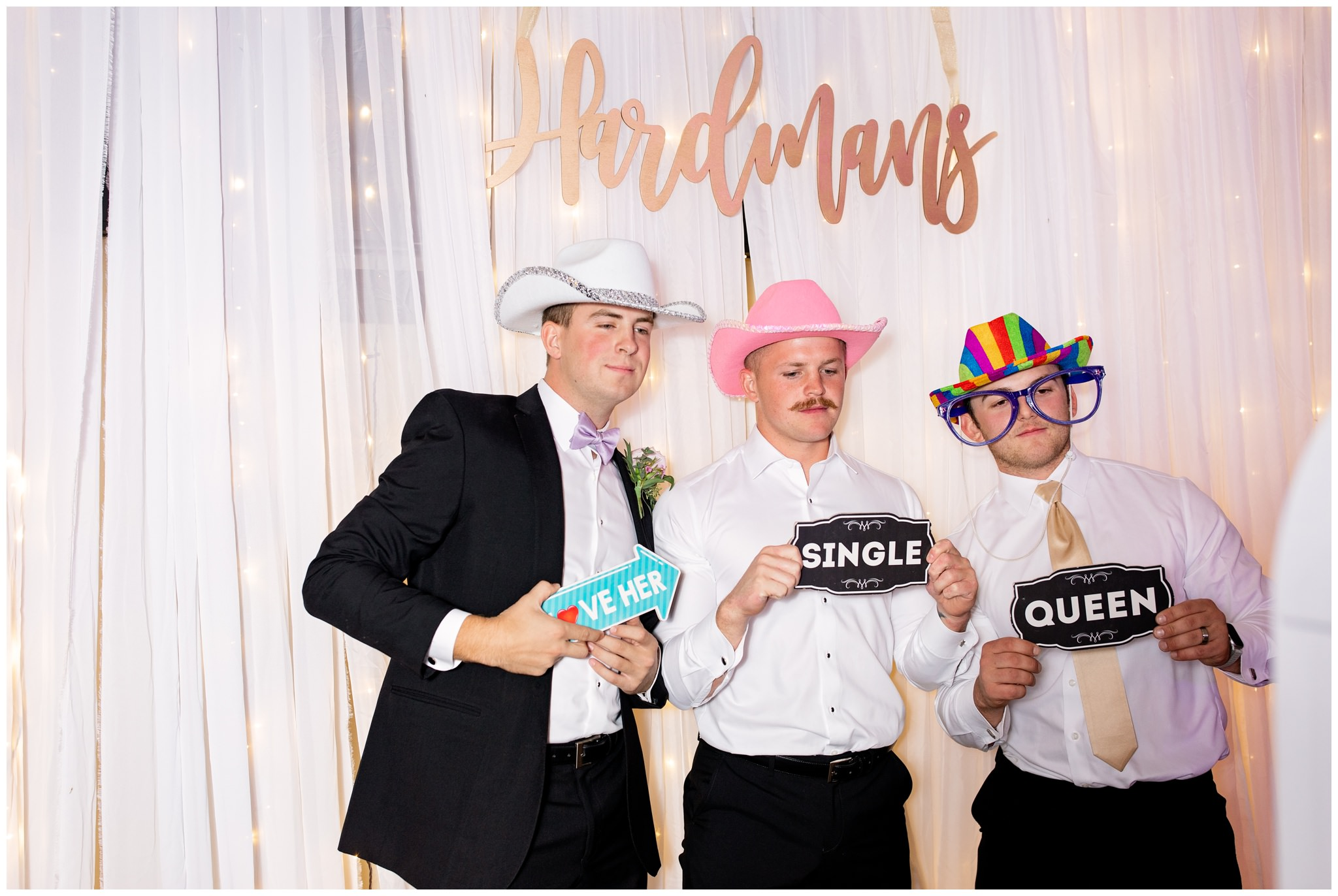 Groom and best friends taking pictures at photobooth