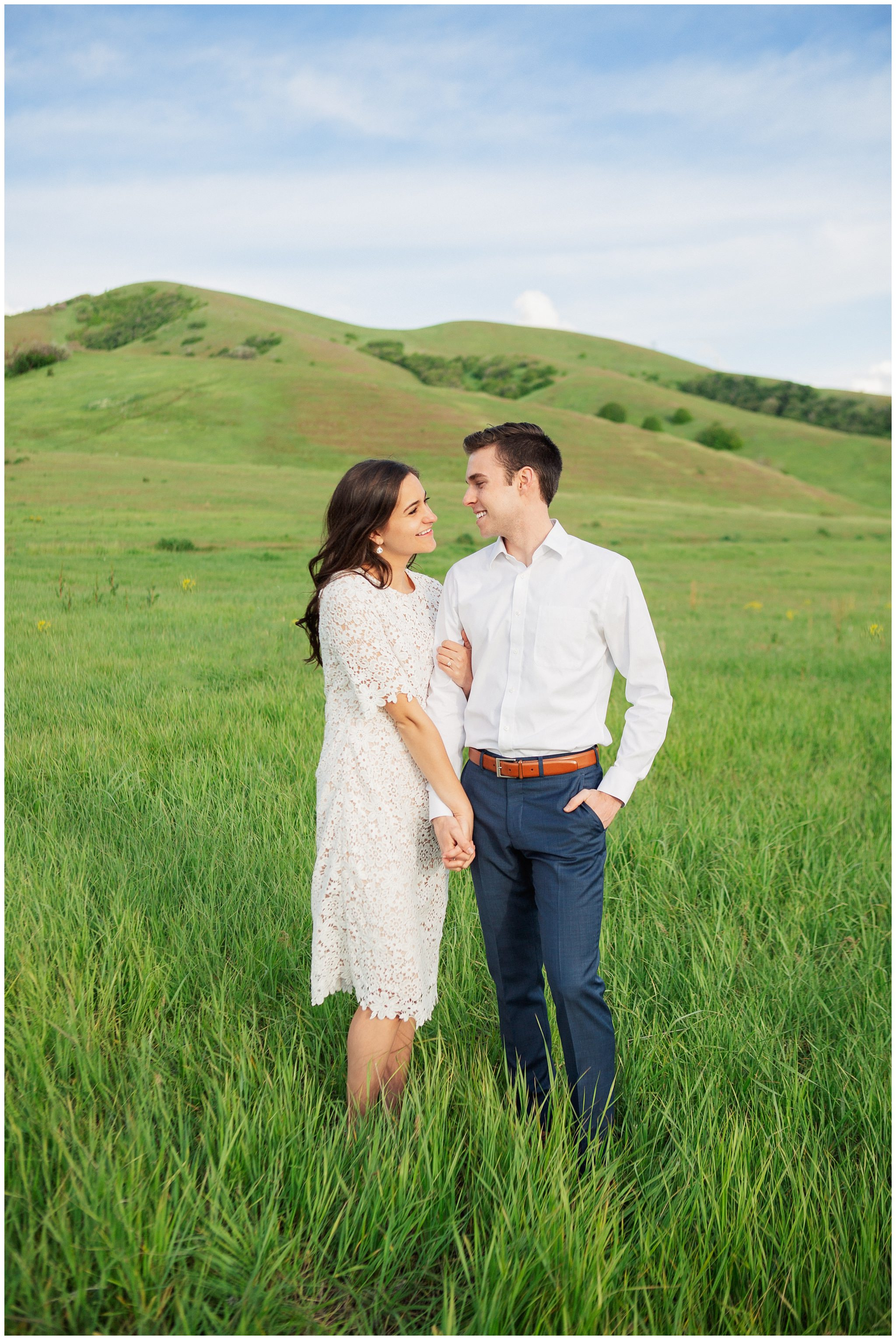 Couple smiling while holding hands for Engagement photos