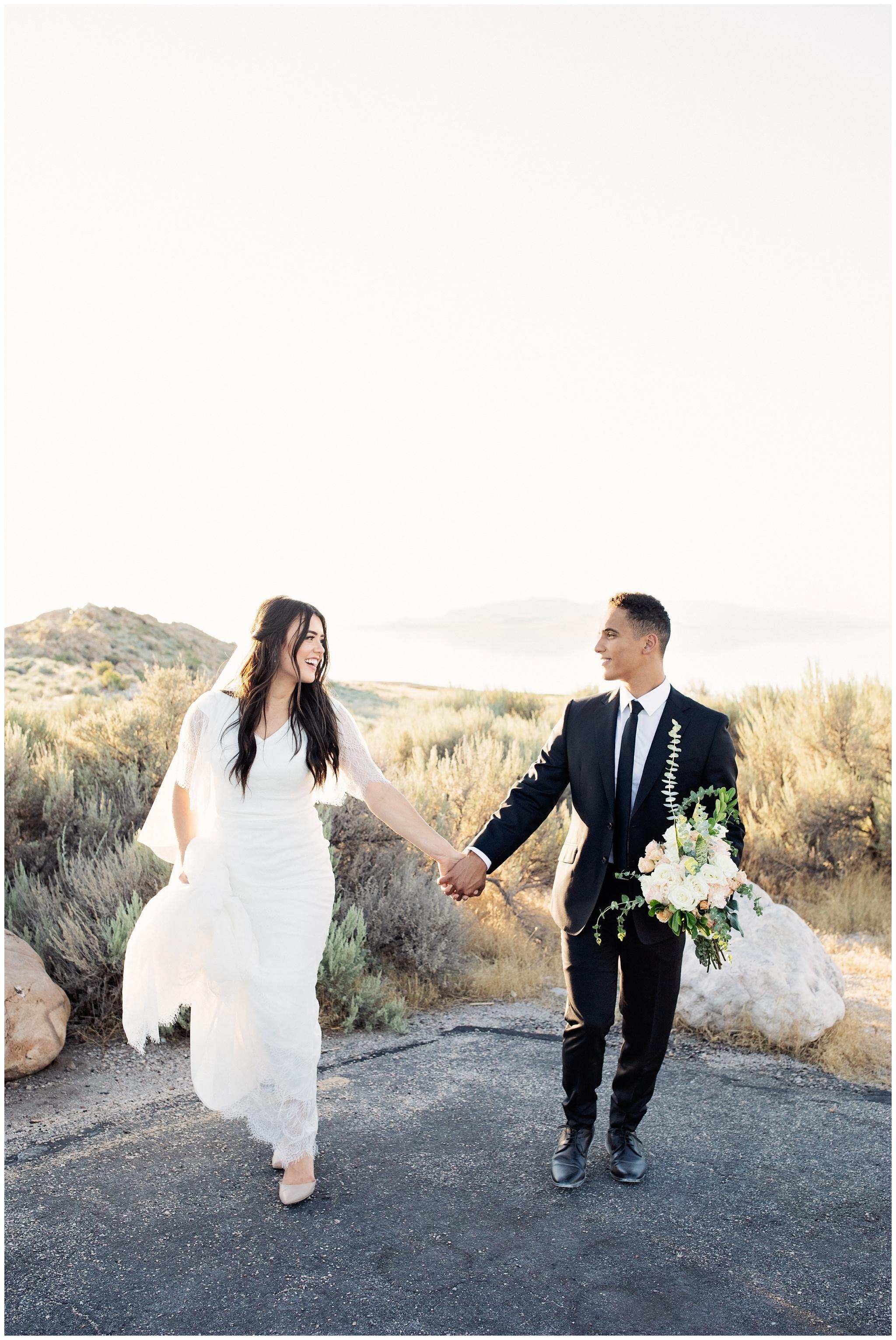 Bride and Groom running towards wedding photographer at Antelope Island