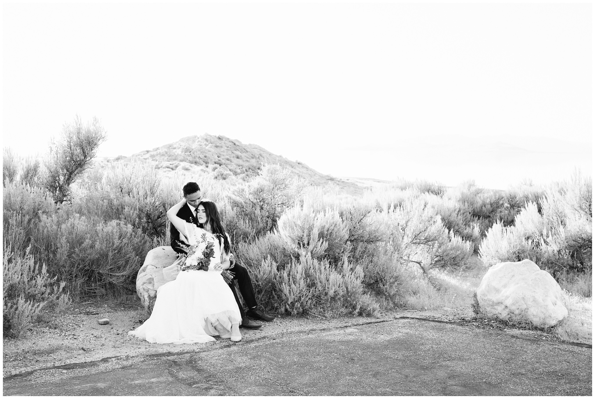 Bride and groom sitting on a rock snuggling at Lady finger point on Antelope island in Utah near SLC