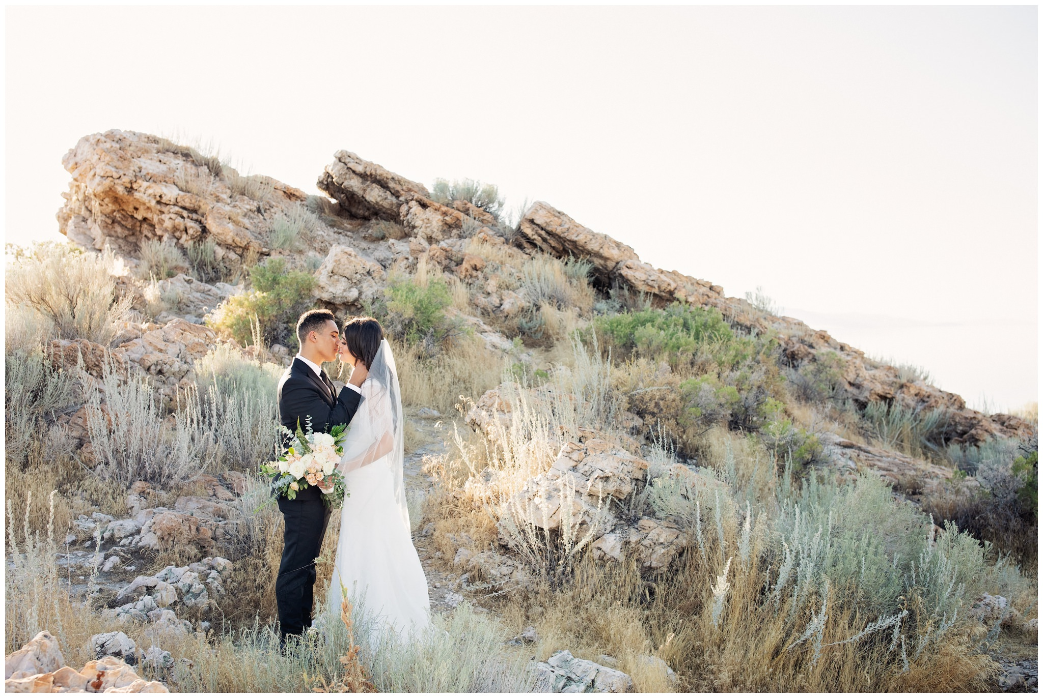 Antelope Island pictures of bride and groom near rocks and island