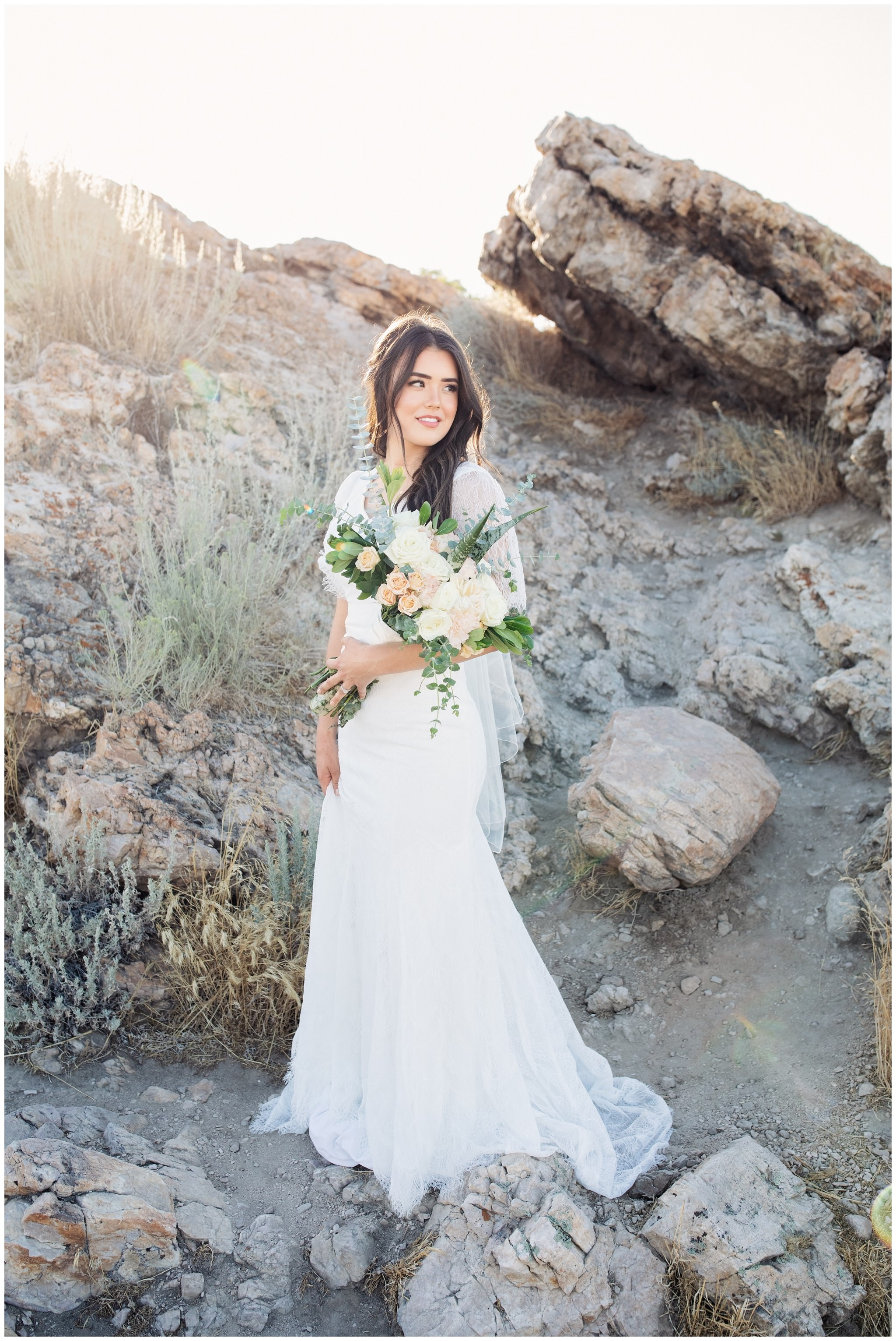 Bride's pictures of her holding wedding bouquet looking off in the distance near rocky background in Utah