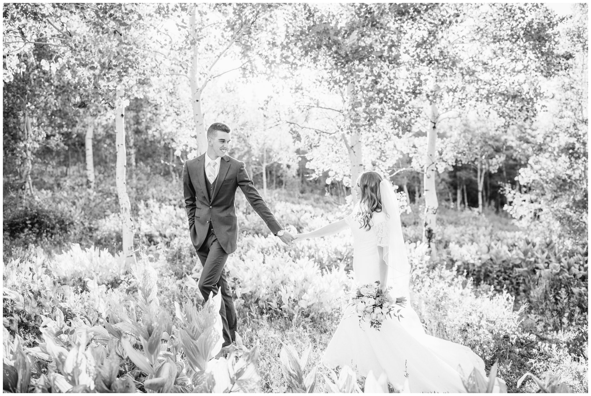 Black and white picture of bride and groom walking in mountains