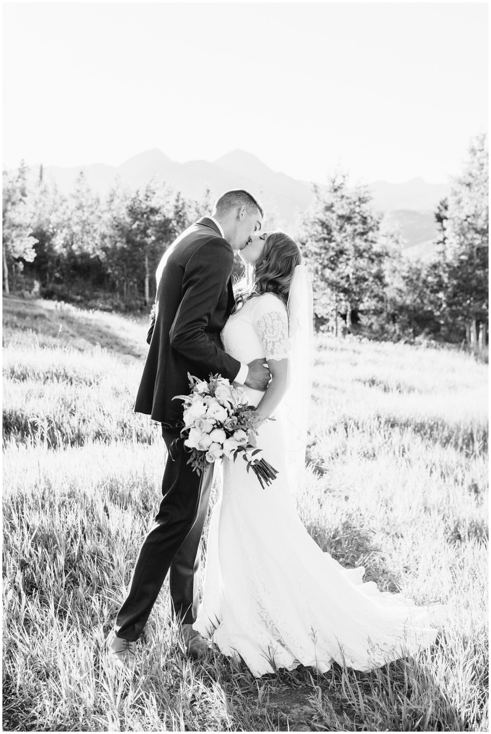 Bride and groom kissing near Aspen trees for their bridals
