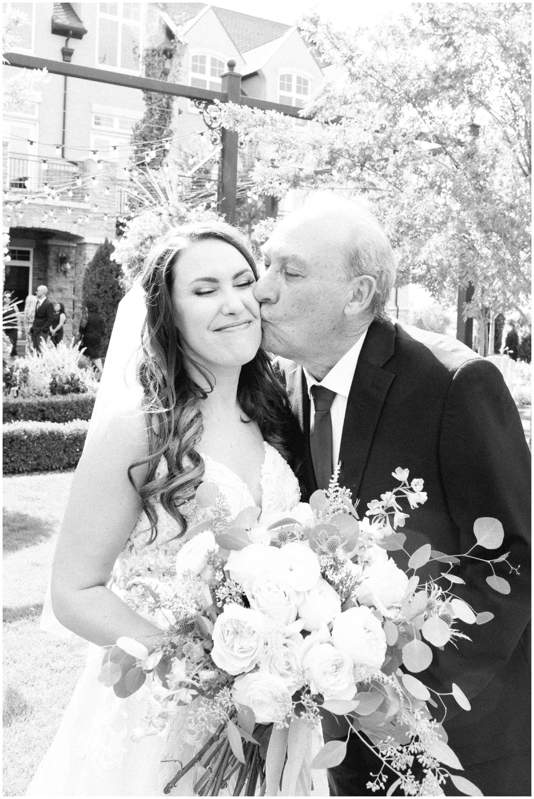 Bride and her dad kissing her cheek
