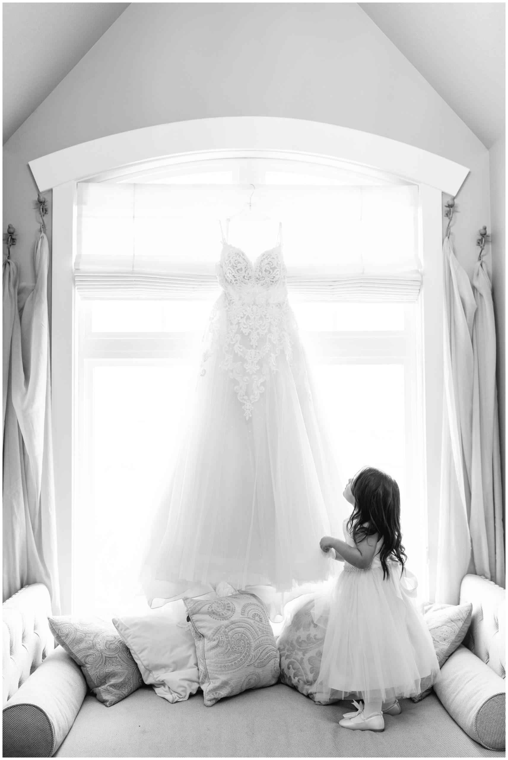 Young daughter looking at her mom's dress hanging in window at Sleepy Ridge in Vineyard Utah