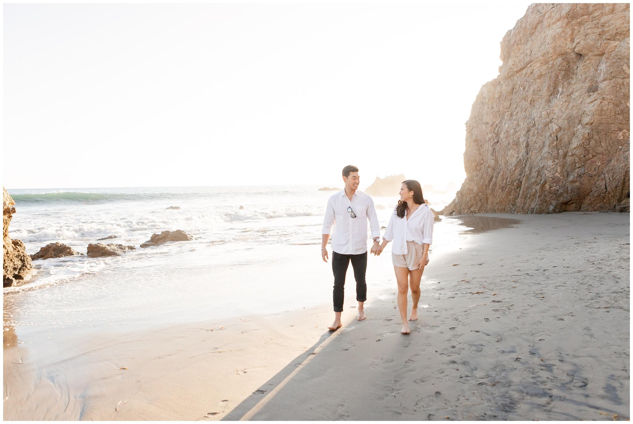 Couple walking on Malibu beach, CA