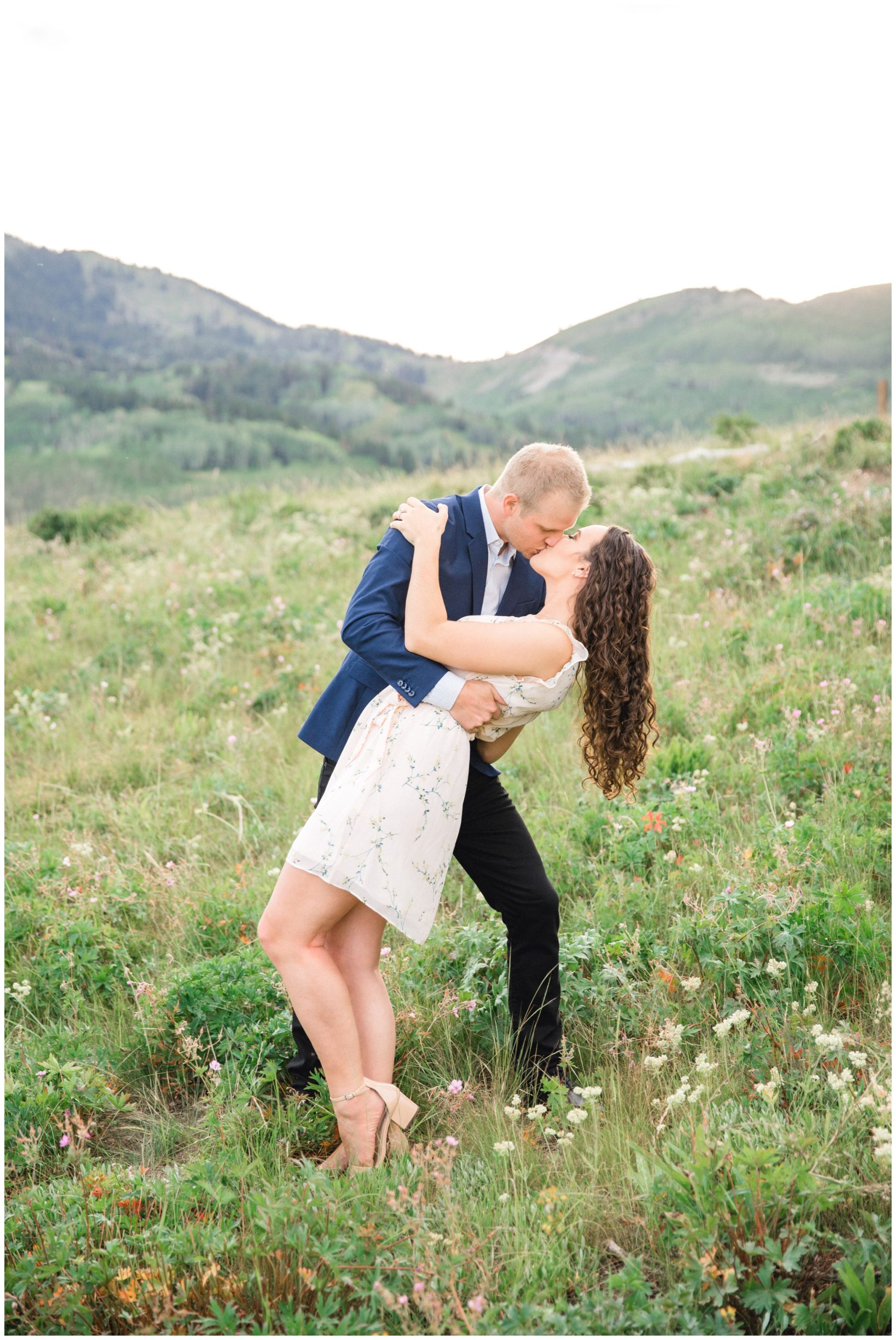 Couple Kissing in a field of flowers for their Engagements in Park City Utah