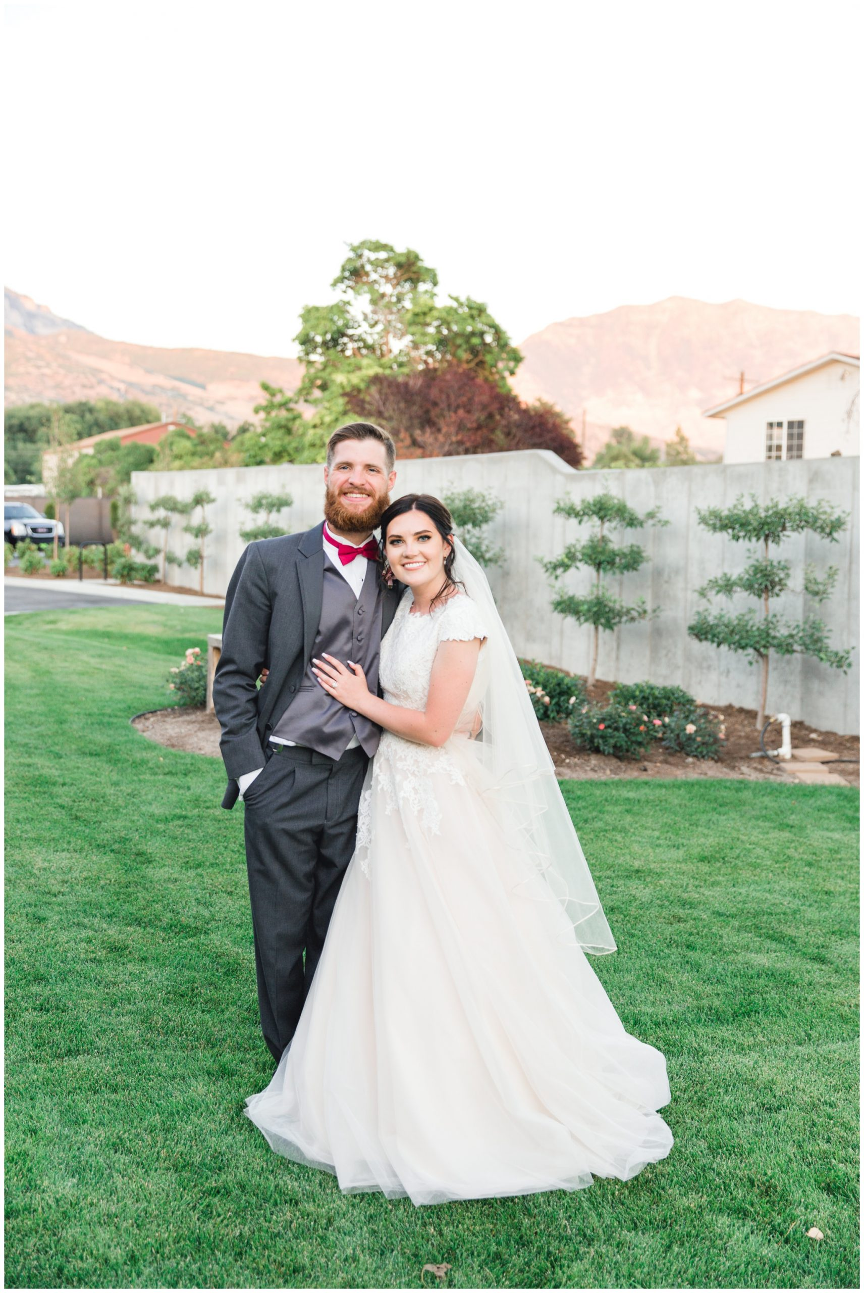 Bride and groom smiling at camera at their reception in Lindon, Utah