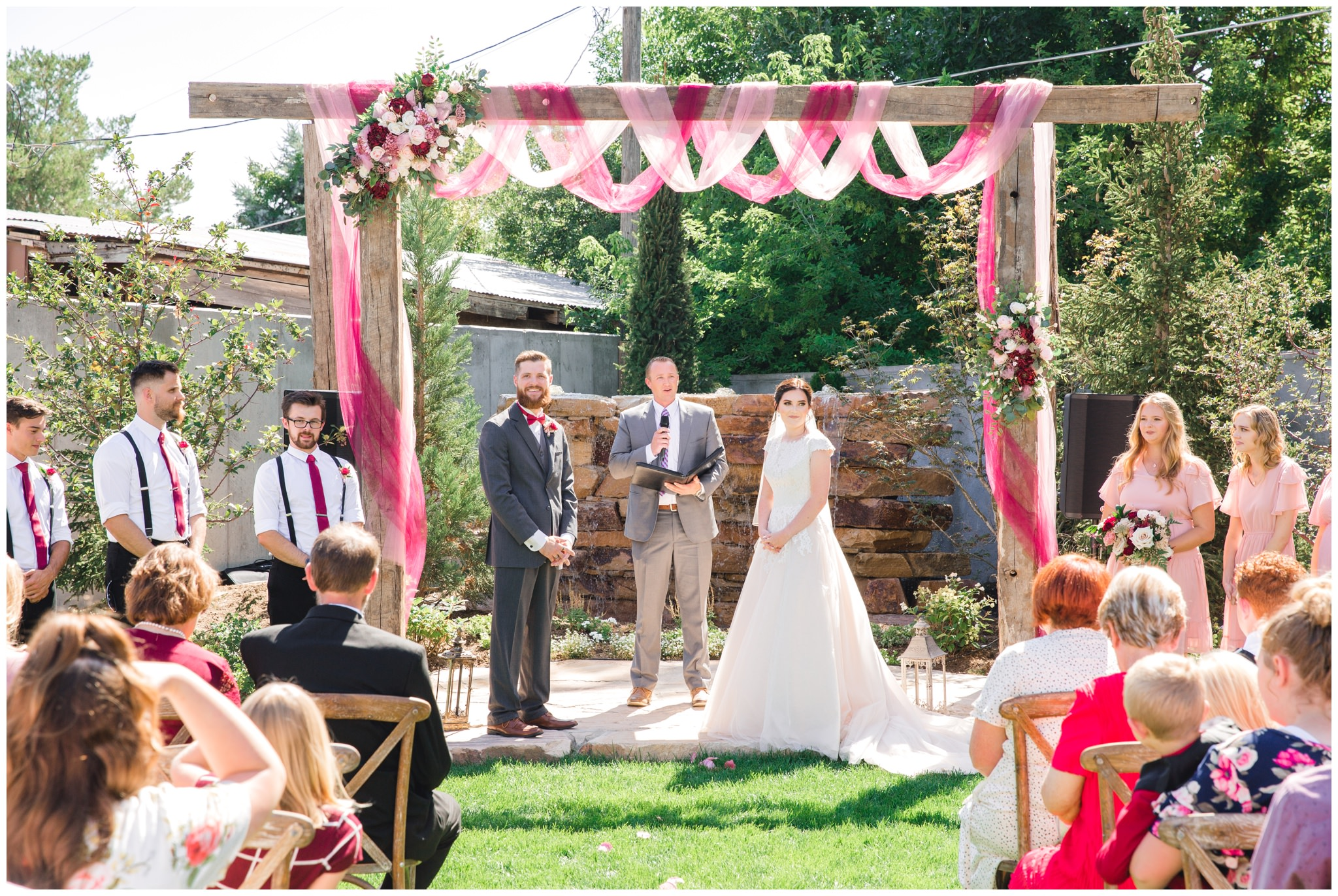 Summer wedding ceremony at the Wild Oak Venue in Lindon, Utah. Burgundy floral arrangement on arch above bride and groom.
