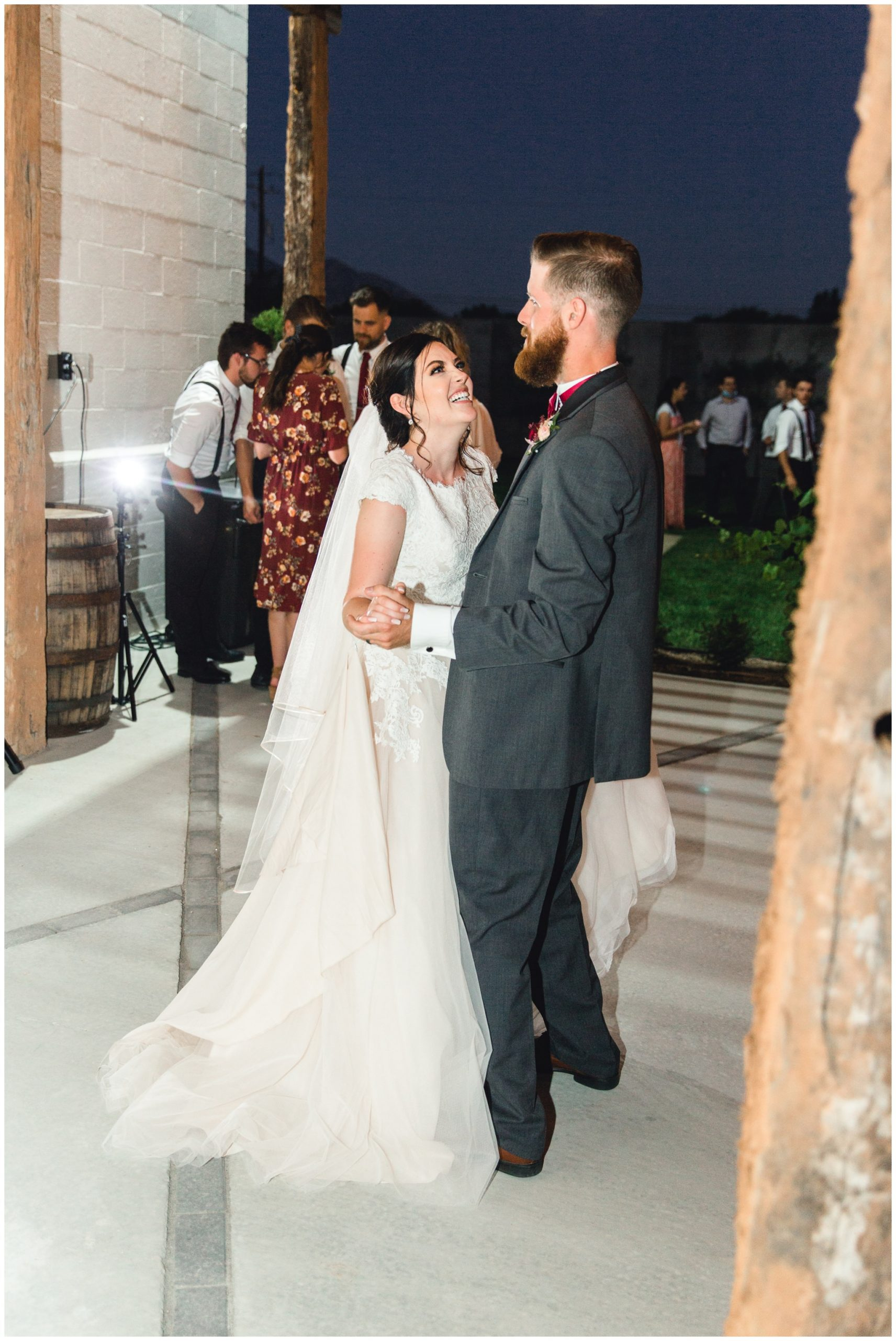 Bride and groom laughing at their wedding reception while dancing together outside of their venue