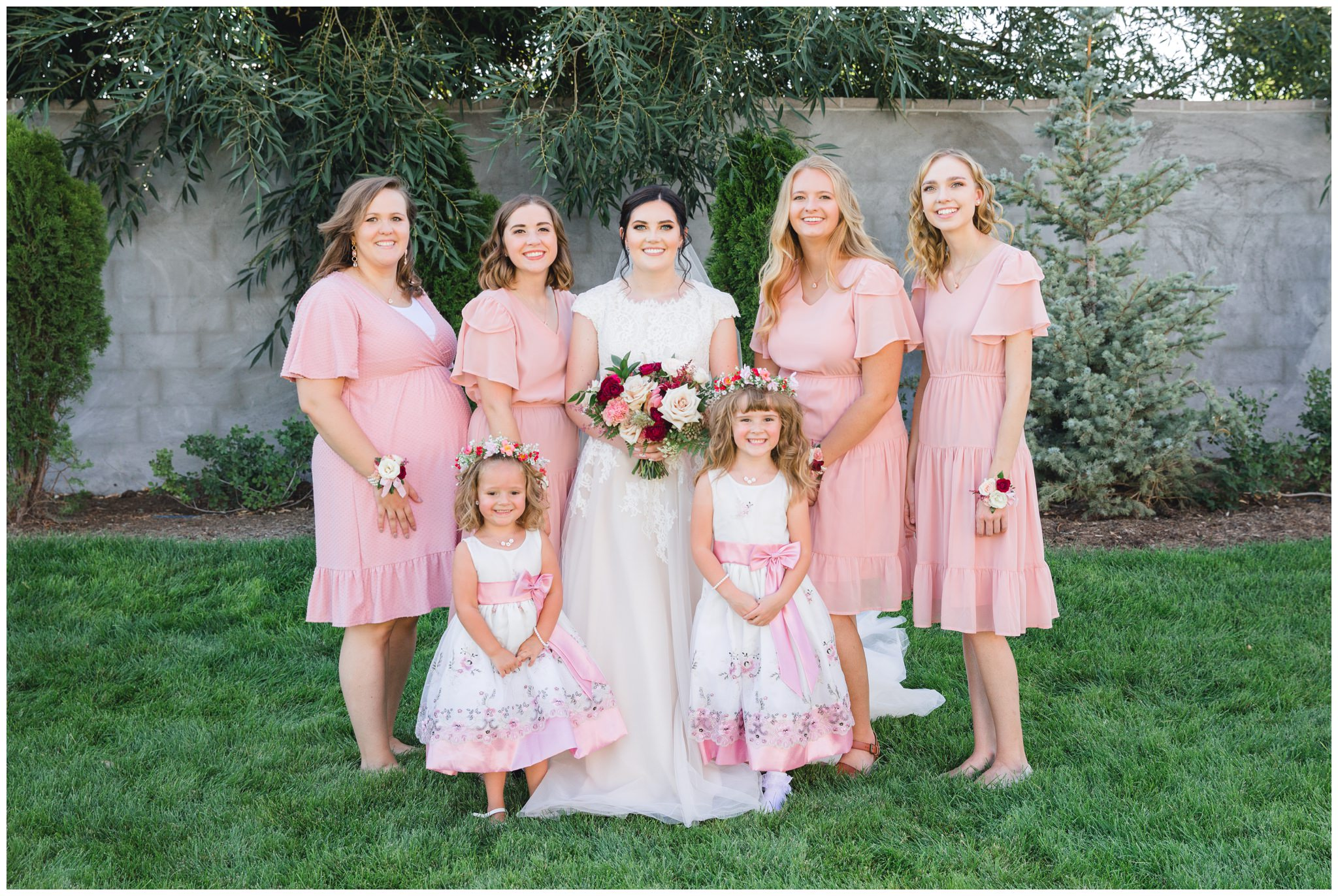 Bride posing with her bridesmaids and flowers girls at wedding in Lindon utah