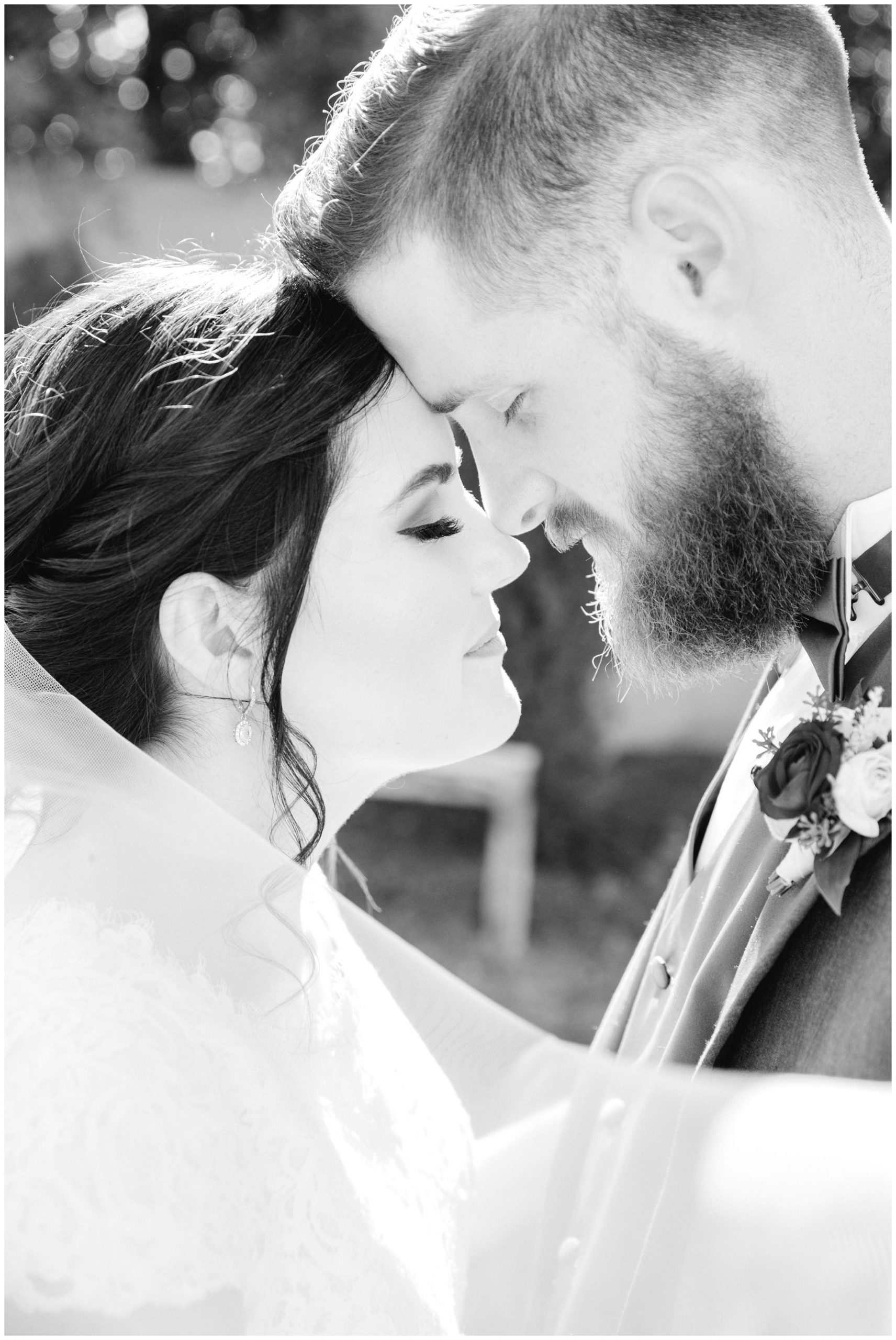 Black and white image of bride and groom snuggling close together at their wedding about to kiss.