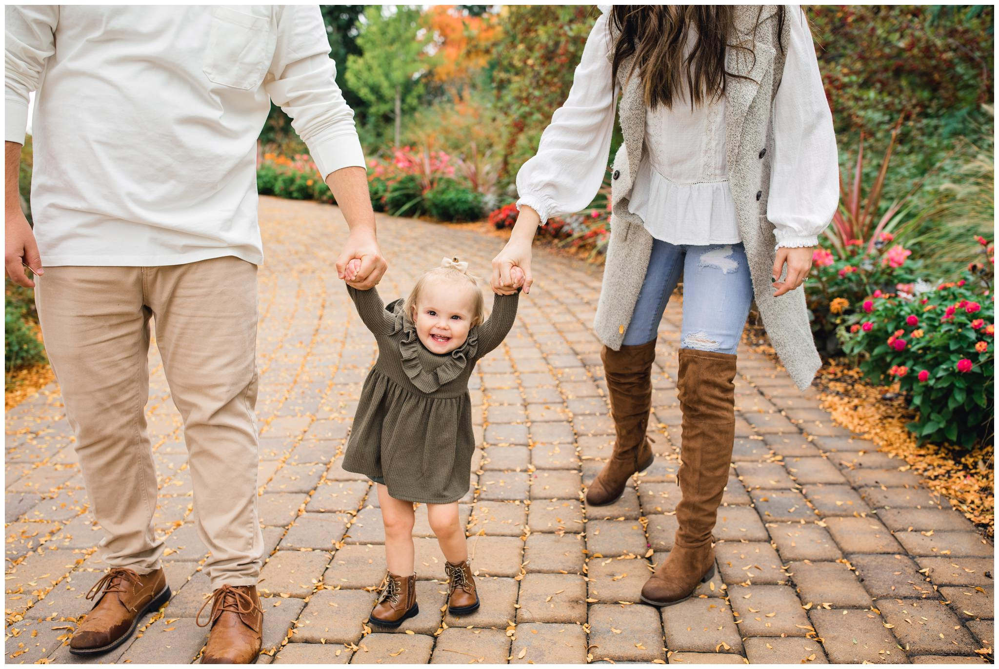 Little baby holding mom and dad's hands while walking