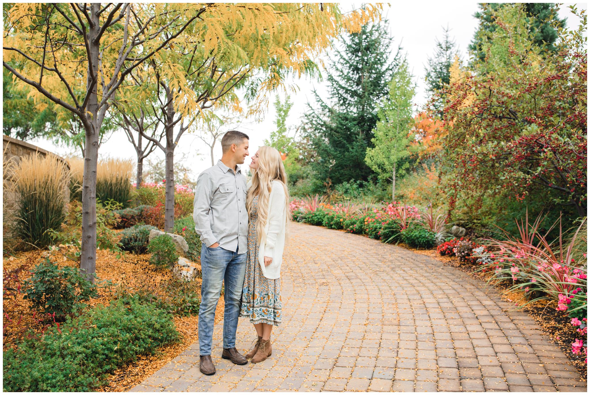 Couple smiling at each other under fall leaves