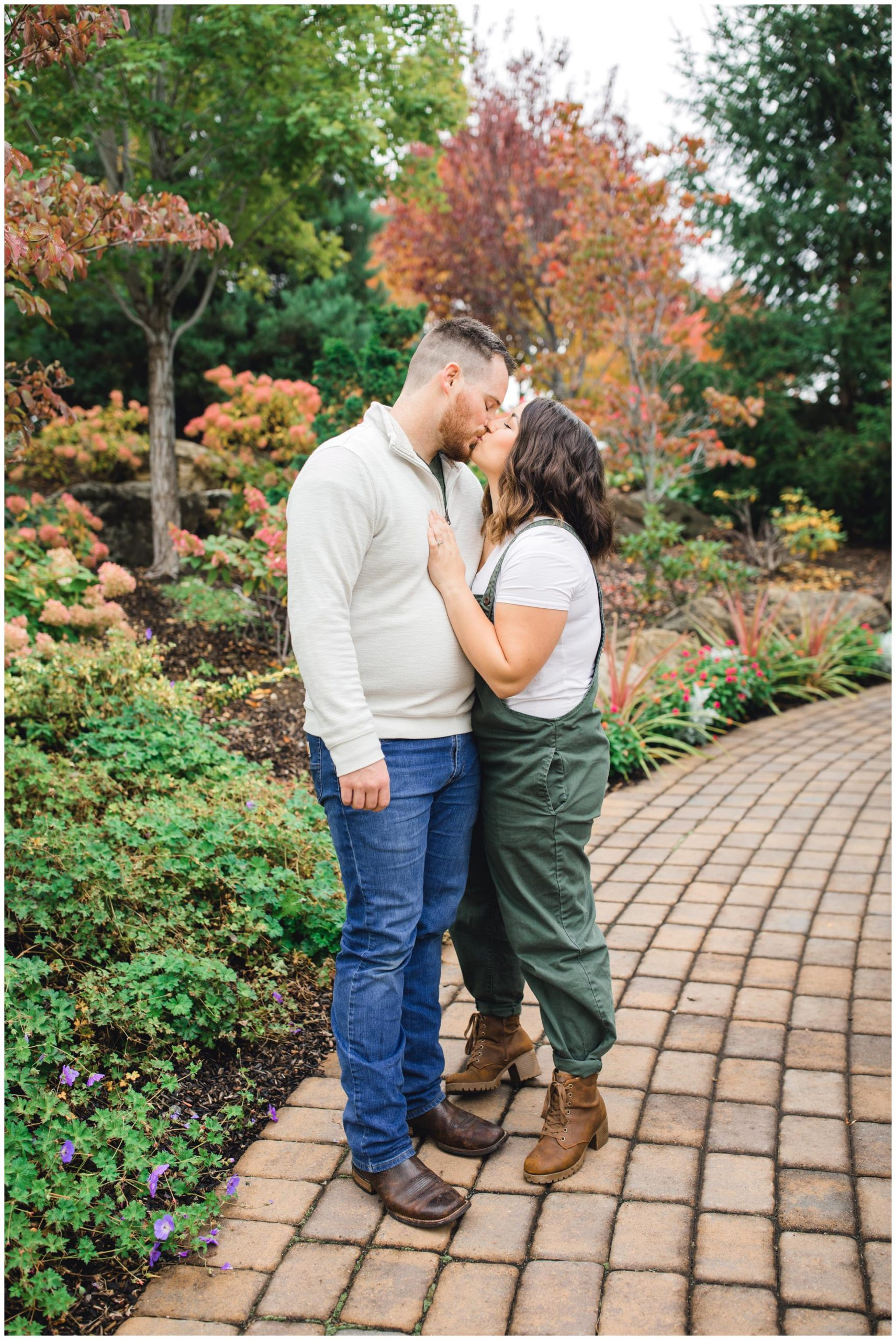 Mom and dad kissing near fall leaves
