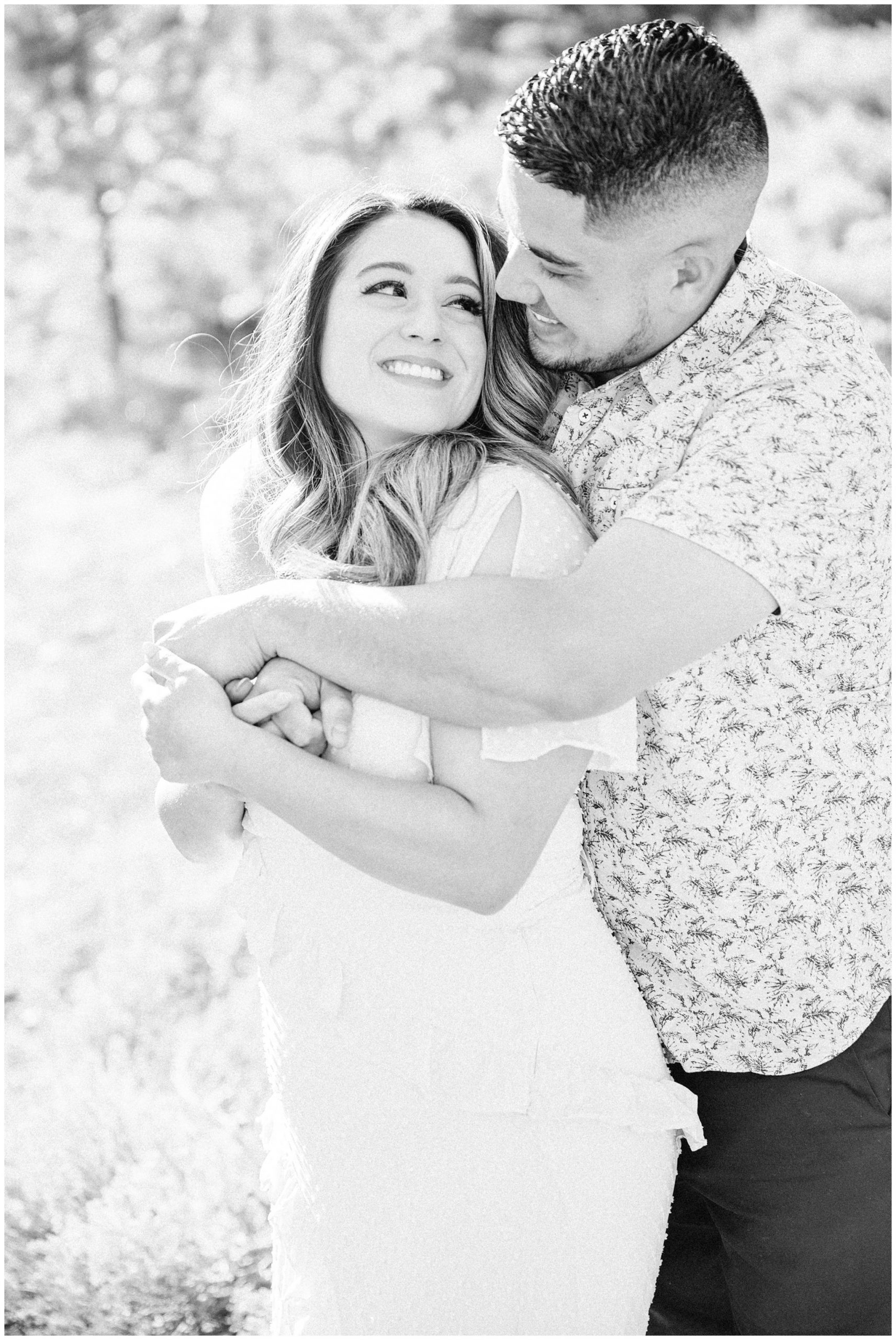 Couple hugging each other during their spring engagement session, black and white image of couple