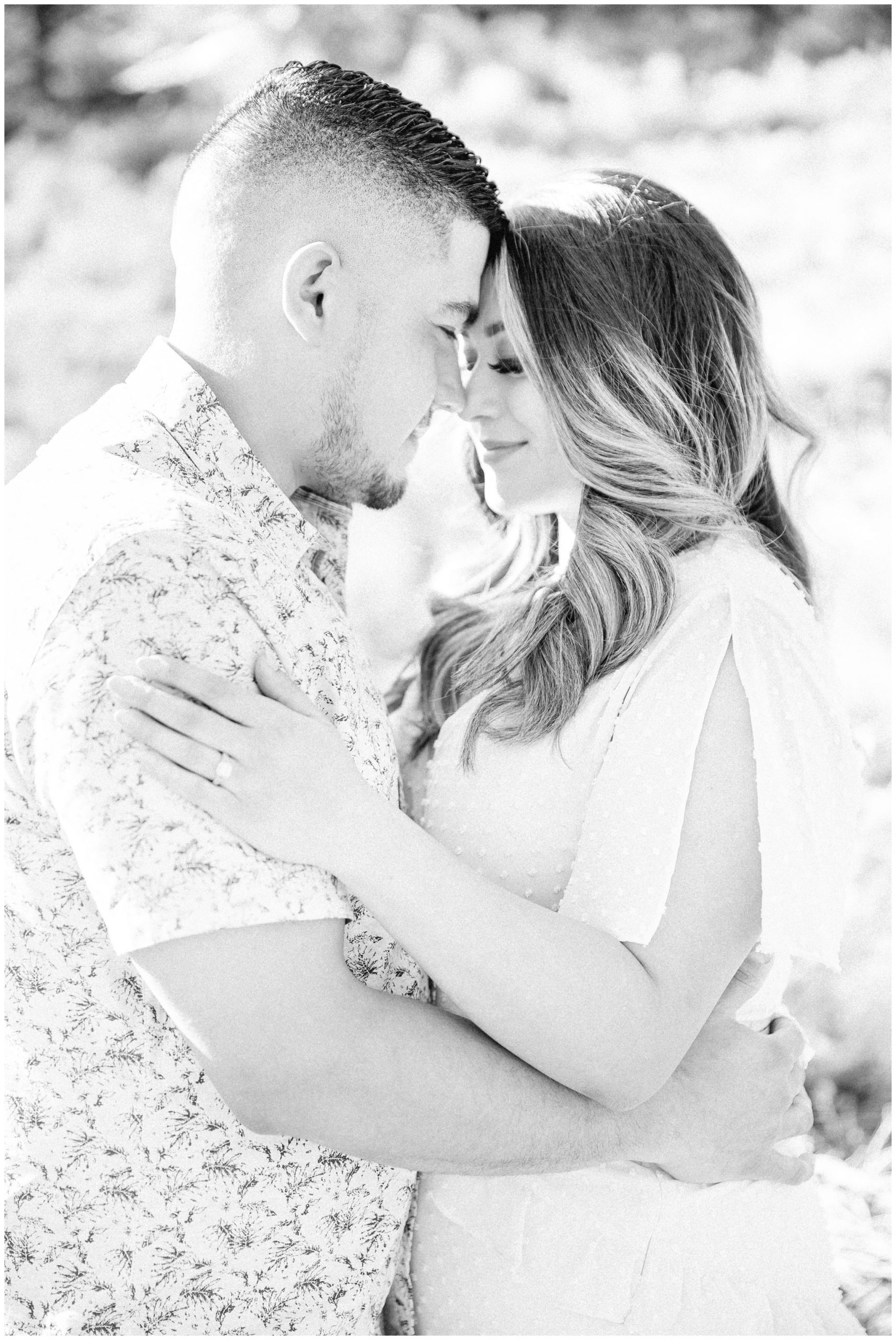 Black and white image of couple snuggling up to each other.