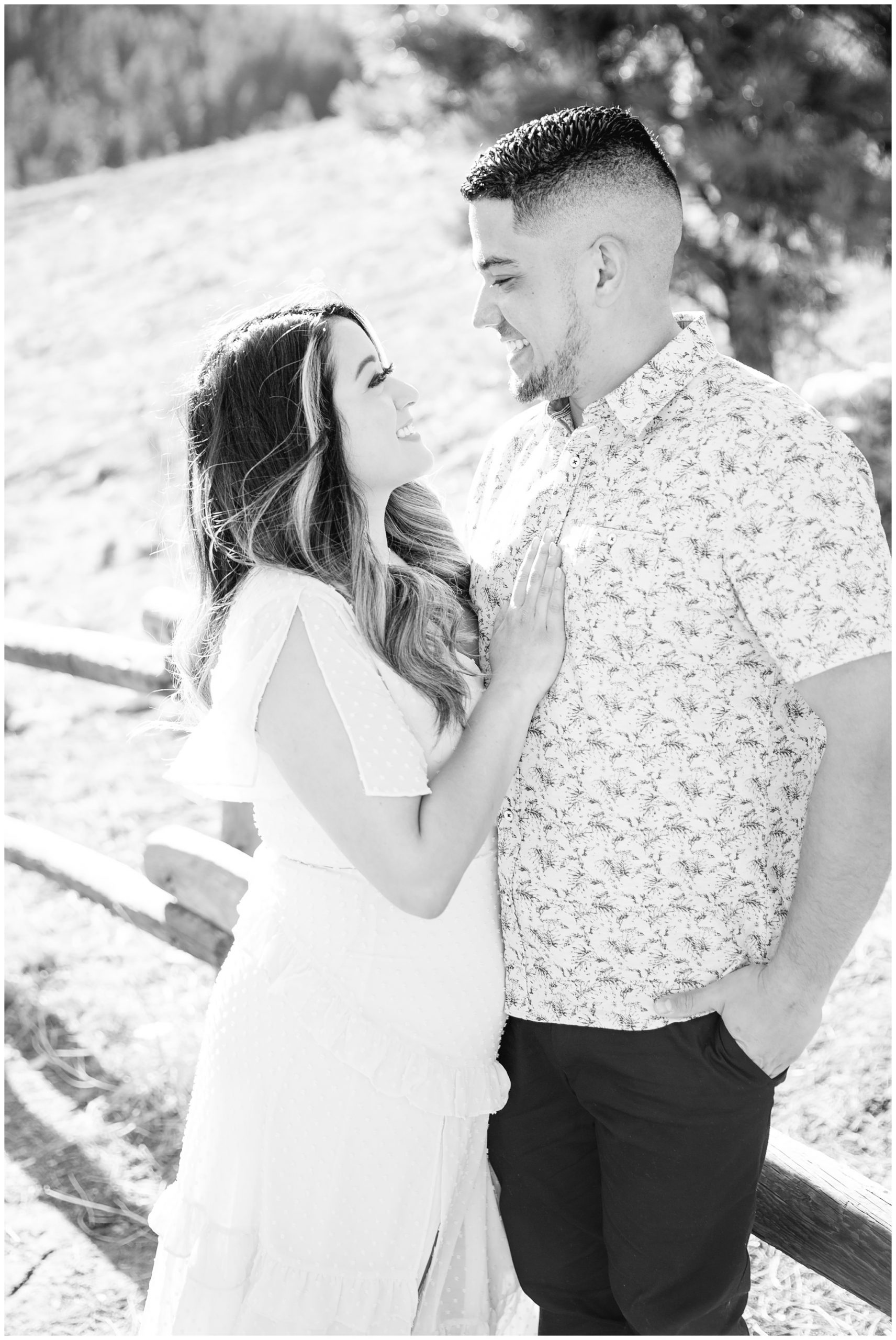 Black and white image of engaged couple smiling at each other