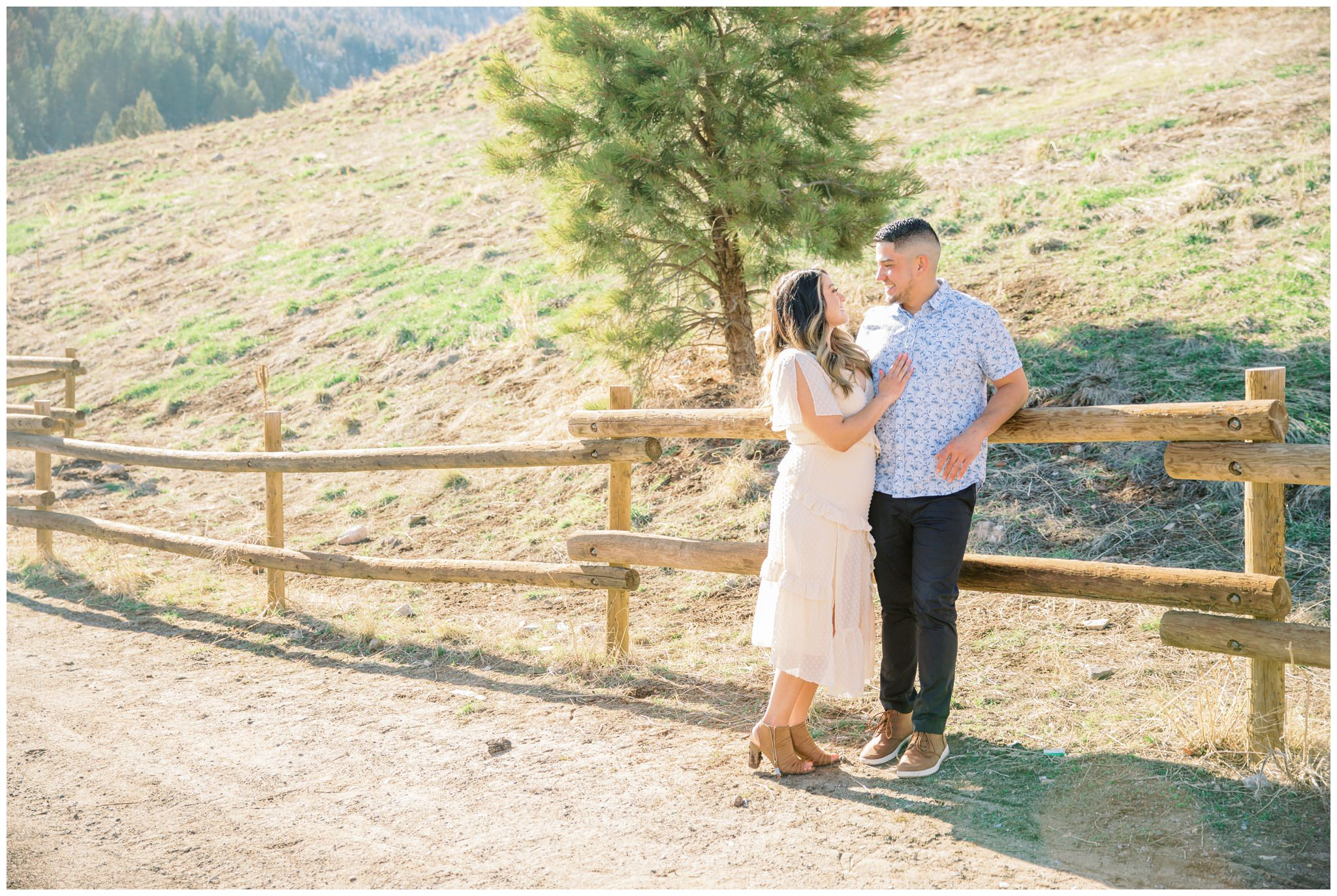 Bride and groom leaning against a wooden fence in the mountains for their engagement pictures in Utah